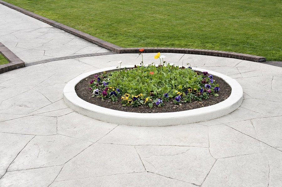 Stamped concrete sidewalk with circular flower garden in the middle